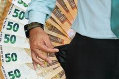 O homem gerencie acima de seu bolso das calças Fundo do euro 50 no fundo foto de stock royalty free