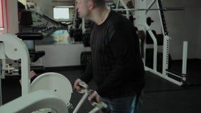 O homem gordo alegre executa um exercício errado no gym Pela primeira vez em um clube de aptidão filme