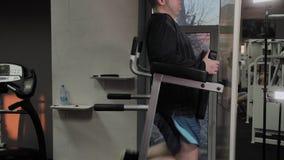 O homem gordo alegre executa um exercício errado no gym Pela primeira vez em um clube de aptidão video estoque