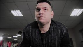 O homem gordo alegre executa um exercício errado no gym Pela primeira vez em um clube de aptidão vídeos de arquivo