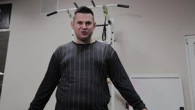 O homem gordo alegre executa um exerc?cio errado no gym Pela primeira vez em um clube de aptid?o vídeos de arquivo