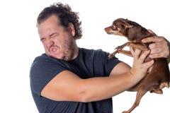 O homem gordo engraçado levanta com pouco cão no fundo branco foto de stock