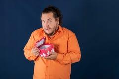 O homem gordo engraçado na camisa alaranjada abre uma caixa com um presente fotografia de stock royalty free