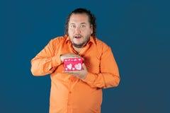 O homem gordo engraçado na camisa alaranjada abre uma caixa com um presente foto de stock royalty free