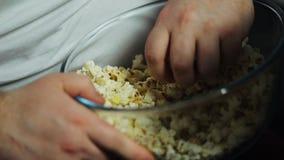 O homem gordo entrega a tomada da pipoca da bacia de vidro, dos programas televisivo de observação e de comer video estoque