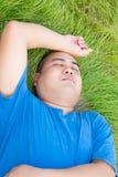 O homem gordo fatigante está encontrando-se na grama verde com esforço Imagens de Stock Royalty Free