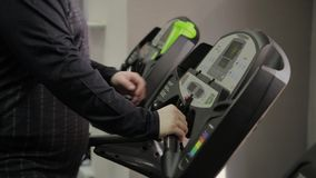 O homem gordo obtém na escada rolante no gym video estoque