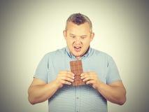 O homem gordo quer tomar uma mordida do chocolate fotografia de stock
