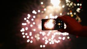 O homem grava os fogos-de-artifício video no telefone esperto filme