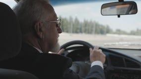 O homem grisalho com uma barba em seu revestimento senta-se atrás da roda de um carro vídeos de arquivo