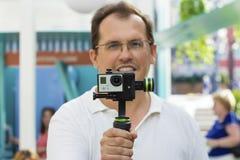 O homem guarda a câmera pequena da ação Fotografia de Stock Royalty Free