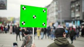 O homem guarda o cartaz com tela verde e passeio da rua com a multidão na reunião da cidade, opinião da parte traseira filme