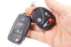 O homem guarda a chave de ignição e o controlo a distância disponivéis da porta da garagem Imagens de Stock