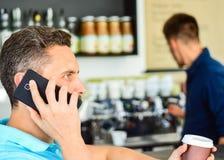 O homem guarda o copo da bebida quando tenha a conversação móvel Café a ir opção útil para povos ocupados Amigo da chamada a ter imagem de stock