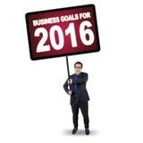 O homem guarda o quadro de avisos com objetivos de negócios para 2016 Fotografia de Stock Royalty Free