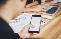 O homem guarda o telefone em uma mesa de madeira no escritório Os membros estão encontrando-se atualmente Os conceitos tecnologic foto de stock
