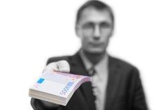 O homem guarda para fora um pacote de notas 500 euro fotografia de stock