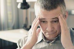 O homem guarda sua cabeça em suas mãos Problemas na vida pessoal e no trabalho stress A enxaqueca  foto de stock royalty free