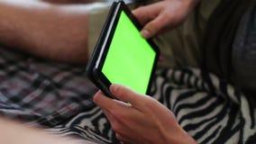 O homem guarda um PC vazio da tabuleta com uma tela verde no sofá video estoque