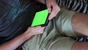O homem guarda um PC vazio da tabuleta com uma tela verde no sofá vídeos de arquivo