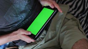 O homem guarda um PC vazio da tabuleta com uma tela verde no sofá filme