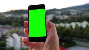O homem guarda um telefone esperto vazio com uma tela verde para seu próprio índice feito sob encomenda video estoque
