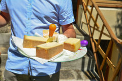 O homem guarda uma bandeja com tipos diferentes de queijos franceses Fotos de Stock Royalty Free