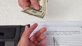 O homem guarda uma cédula do dólar em sua mão e dá-a à mão da mulher imagem de stock