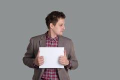O homem guarda uma folha de papel limpa Fotografia de Stock