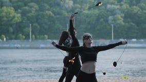 O homem hábil e duas mulheres na roupa e em máscaras pretas executam uma mostra com a chama ao estar no riverbank h?bil vídeos de arquivo