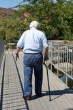 O homem idoso com um bastão anda afastado Imagem de Stock