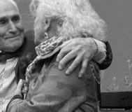 O homem idoso elegantemente vestido abraça ombros idosos do ` s da mulher Imagem de Stock