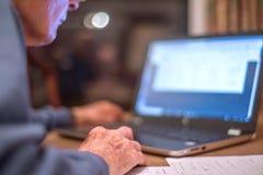 O homem idoso em um laptop verifica sua operação bancária em linha, Hampshire, Inglaterra, U K foto de stock