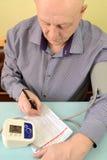 O homem idoso escreve para baixo indicadores no diário do controle da pressão arterial Fotos de Stock