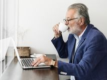 O homem idoso está usando o portátil do computador imagens de stock