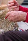O homem idoso faz cestas para o uso na indústria de pesca na maneira tradicional, em Gallipoli, Puglia, Itália fotos de stock
