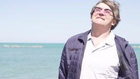 O homem idoso feliz com vidros anda pelo mar na queda filme