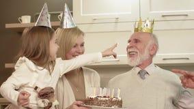 O homem idoso funde para fora velas no bolo vídeos de arquivo
