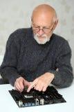 O homem idoso instala o processador central ao cartão-matriz Foto de Stock