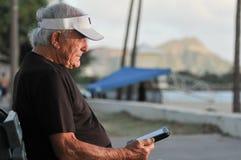 O homem idoso lê o ebook no banco pela praia Imagens de Stock