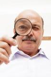 O homem idoso olha algo através de uma lupa Fotografia de Stock Royalty Free