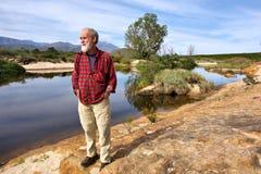 O homem idoso olha o por do sol ao lado do rio Imagens de Stock Royalty Free