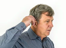O homem idoso põe em sua prótese auditiva Imagens de Stock Royalty Free