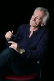 O homem idoso pensativo com os monóculos nas mãos Fotografia de Stock Royalty Free