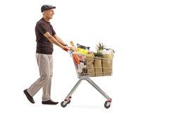 O homem idoso que empurra um carrinho de compras encheu-se com os mantimentos imagens de stock