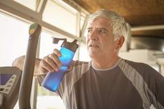 O homem idoso que guarda uma garrafa da água O homem é refrescado foto de stock
