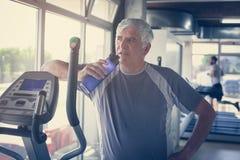 O homem idoso que guarda uma garrafa da água fotos de stock