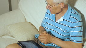 O homem idoso usa a tabuleta vídeos de arquivo