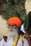 O homem indiano que vende o pavão empluma-se no forte de Jaisalmer, Índia Fotografia de Stock Royalty Free