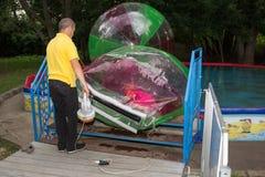 O homem infla o zorb com menina foto de stock royalty free